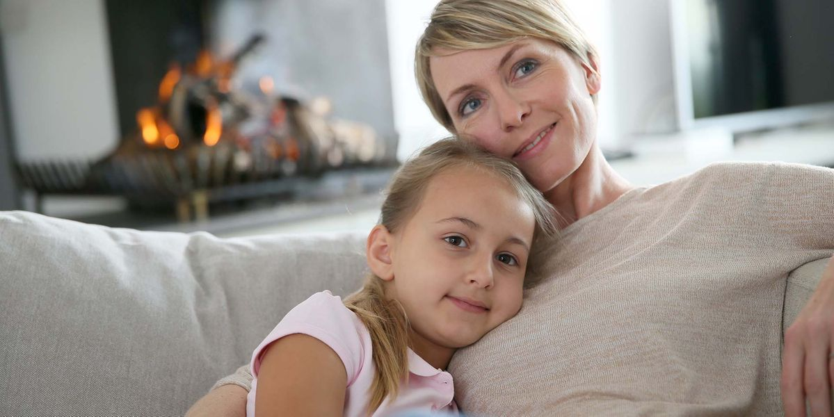 Mother and daughter relaxing by fireplace